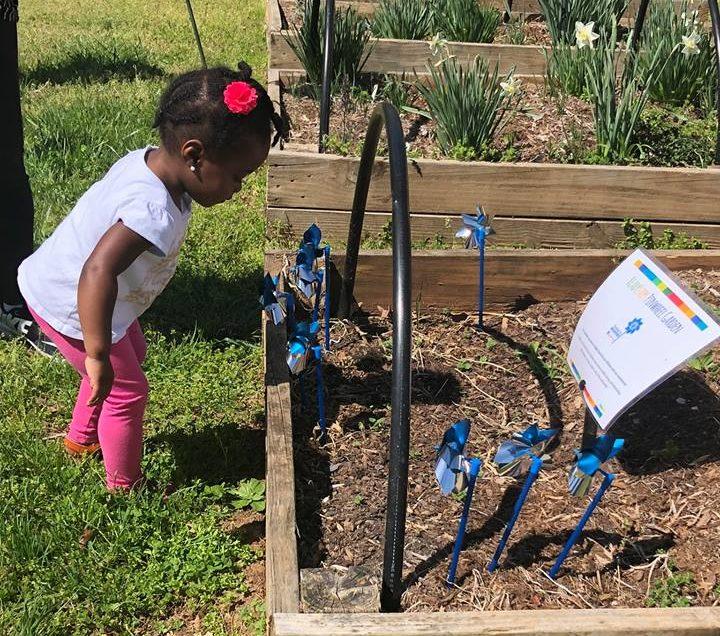 little girl blowing a blue pinwheel