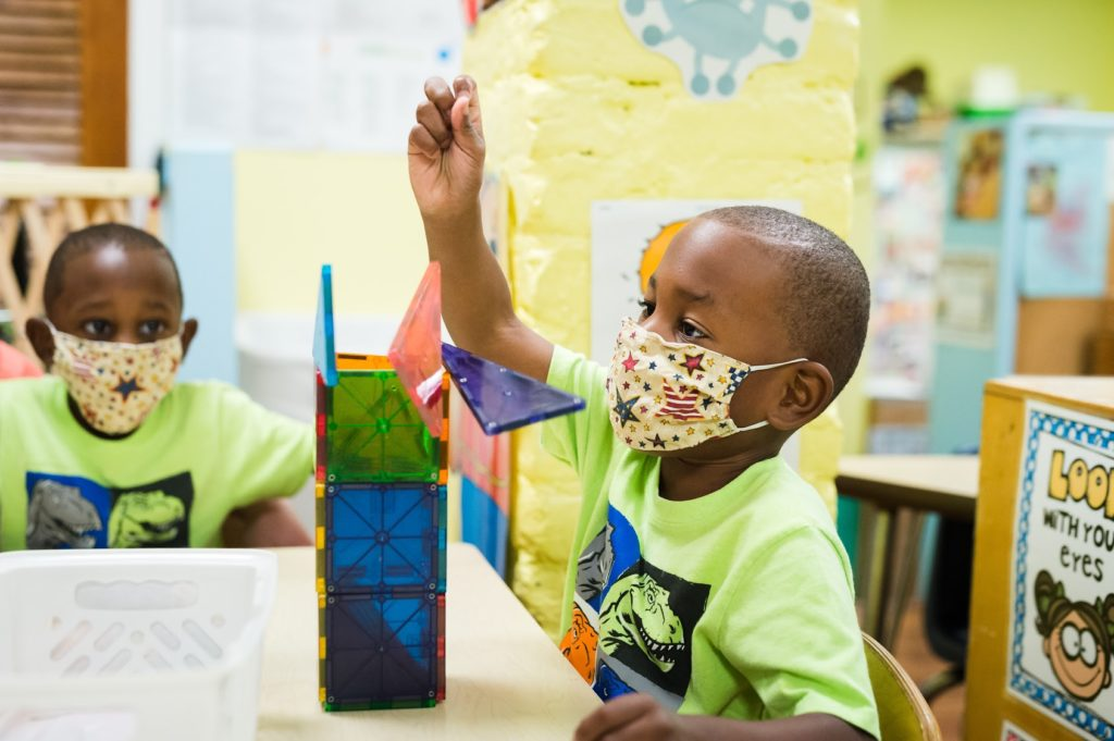 child in mask builds with magnatiles